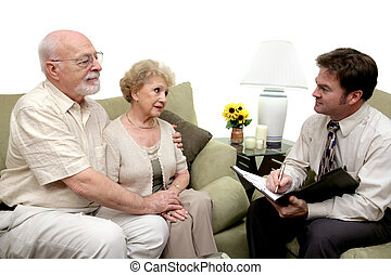 A senior couple speaking with a marriage counselor. Could also be a salesman in their home. Isolated on white with focus on couple.