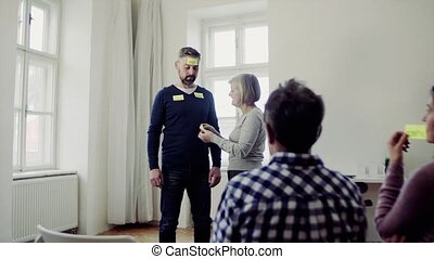 Counsellor putting adhesive notes with negative words on client during group therapy.
