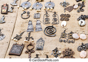counter medieval jewelry pendant, earrings, brooch with a pattern of Celtic patterns laid out on a fabric background