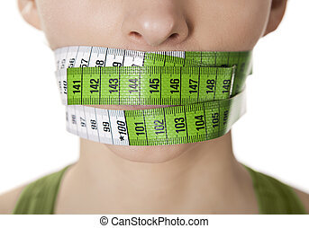 Portrait of a young woman with a green measuring tape covering the mouth