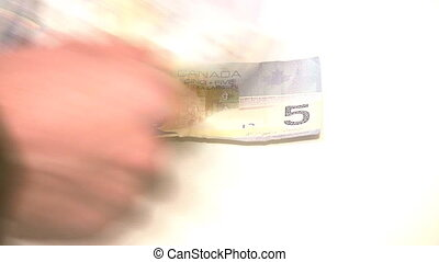 Counting Canadian money and coin isolated on white -...