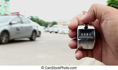 counting cars with counter clicker machine - close up...
