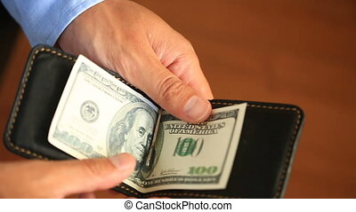 Men's hands hold a money clip with dollars