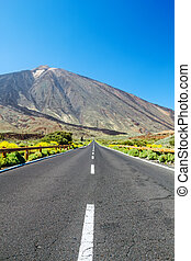 Country asphalt road background with focus on foreground and blurred landscape.
