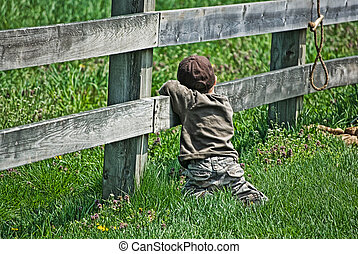 Country Boy - Little boy leaning on a country fence.