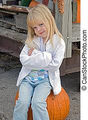 Country Bumpkin - Little blond girl on a pumpkin.
