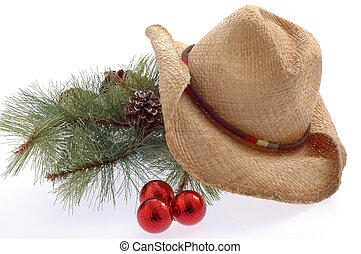Pine bough and well worn cowboy hat on white background.