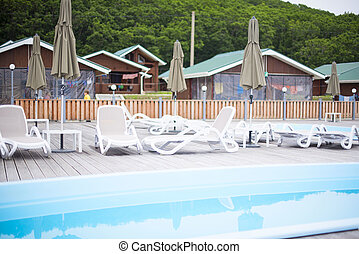 Country club recreation recreation relax pool wooden house forest trees sun lounger umbrella.