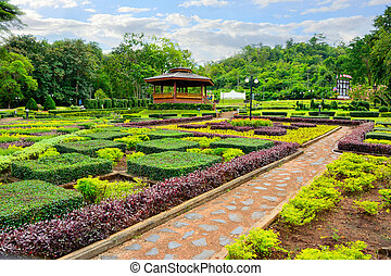 Country cottage garden path. Thai style pavilion is located in the middle with tree background