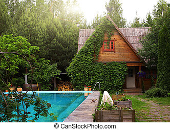 country cottage house with ivy facade and open air swimming pool