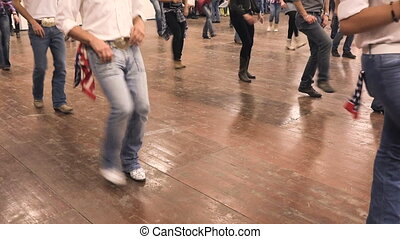 Country dance on rough wood floor. People dancing at folk...