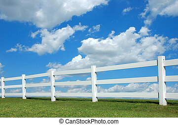 White fence against a bright sky with clouds