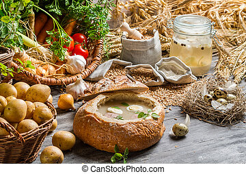 Country Fresh sour soup served in bread with marjoram