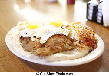 Country fried steak with gravy along with eggs sunnyside up ...