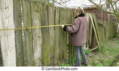 Country girl measures old fence with tape measure
