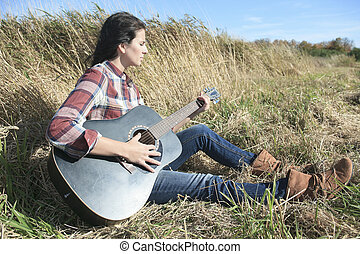 Country hippie girl with guitar at wheat field drinking black ca