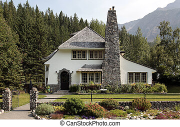 Country home with large brick chimney and mountain backdrop