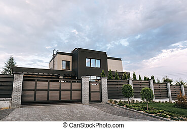 Country house with a flat roof and large windows in brown and beige colors. Exterior. Entrance group: gate and wicket. Fence: brick posts with sections of horizontal wooden planks. Landscaping design