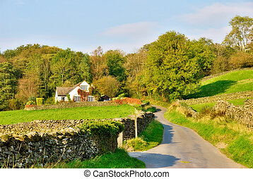 An English country lane lined with dry-stone walls, leading to a house