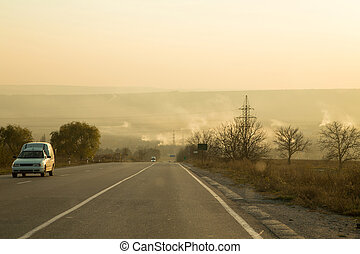 Country long asphalt road on sunset.