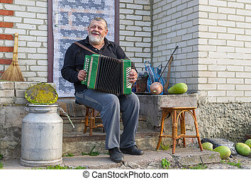 Country-man playing button accordion (garmon) at the doorway