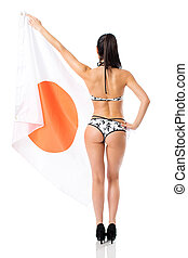 Country of the rising sun. Young beautiful brunette woman in bikini holds up a clear flag of Japan