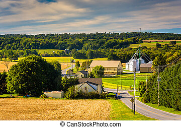 Country road and view of silo and barn on a farm in rural York County, Pennsylvania.