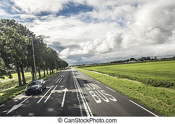 Country road with beautiful markings, against a contrasting cloudy sky.
