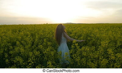 Country side girl in white dress spinning at sunset in a tall field of canola flowers
