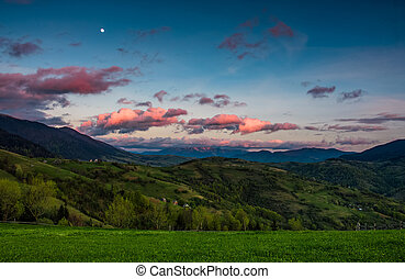 countryside landscape in mountains at dusk and moonrise -...