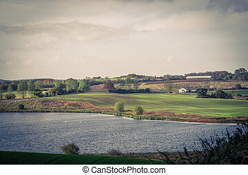 Countryside landscape with a farm and a lake