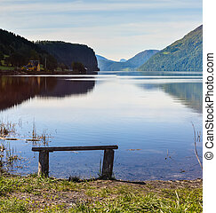 wooden bench on a lake in the mountains