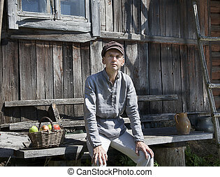 Countryside man - Male farmer sitting in front of wooden...