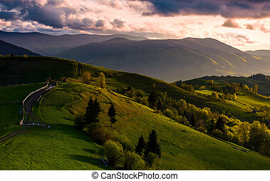 countryside road through grassy hills at sunset -...