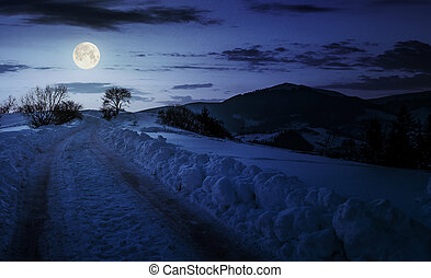 countryside road uphill in snow at night in full moon light....