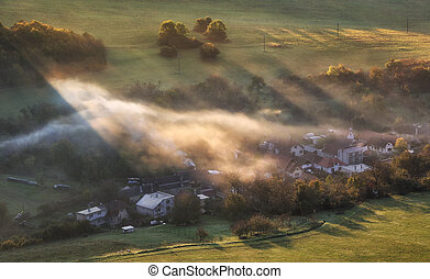 Countryside rural landscape with village over sunbeam in misty morning.