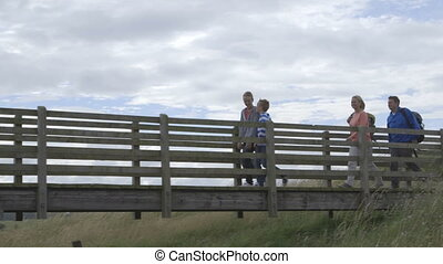 Countryside Walks - Family of four walking across a bridge...