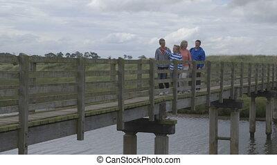 Countryside Walks - Family of four walking across a bridge ...