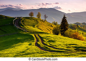 countryside with grassy slopes at sunset. wooden fence along...