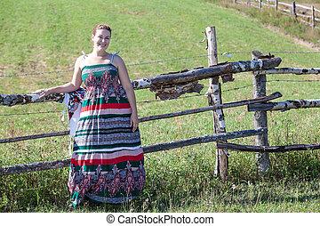 Countrywoman in sundress standing near village fence in field. Copyspace