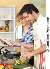 Coupe cooking in kitchen with cookbook