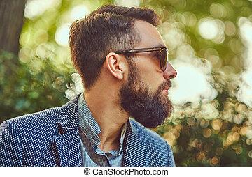 coupe, gros plan, mâle, séance, barbu, lunettes soleil, veste, park., portrait, élégant, banc