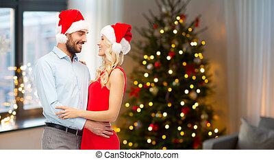 couple étreindre, noël, santa, chapeaux, heureux