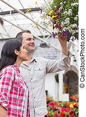 Couple admiring hanging flower basket