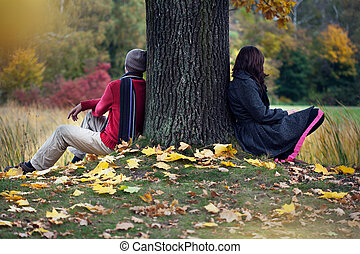 Couple after arguing sitting in autumn park