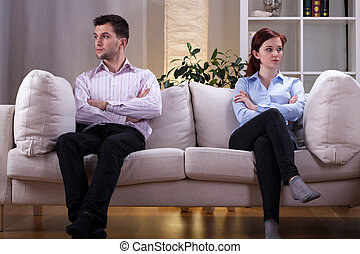 Couple after quarrel - Young couple sitting on the sofa...