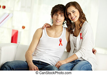 Couple against AIDS - Tilt up of young smiling couple...