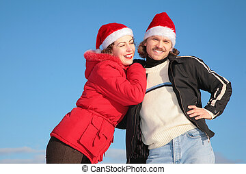 couple against blue sky background in winter in santa claus hats