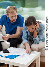Couple analyzing home budget - Couple sitting on sofa and...