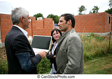 Couple and agent looking at a new-build holding a laptop with the screen left blank for your image